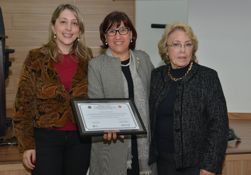 Reitora Cleuza Dias recebendo homenagem do Cenpre das professoras Cristiane Marcos e Eli Sinnott